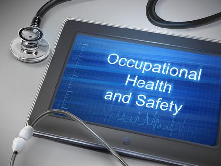 テーブルの上に聴診器でタブレットに表示される産業保健及び安全性の言葉