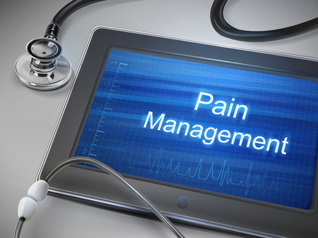 chronic back pain: pain management words displayed on tablet with stethoscope over table