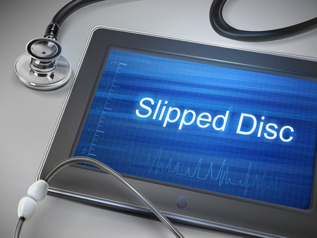 paralysis: slipped disc words displayed on tablet with stethoscope over table
