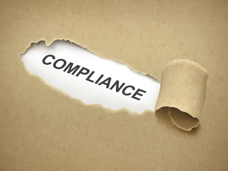 the word compliance behind brown torn paper