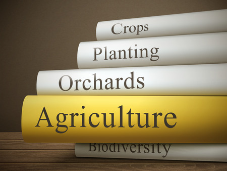 yields: book title of agriculture isolated on a wooden table over dark background
