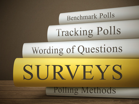 surveys: book title of surveys isolated on a wooden table over dark background