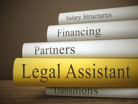 law book: book title of legal assistant isolated on a wooden table over dark background