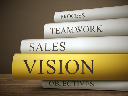 sales team: book title of vision isolated on a wooden table over dark background