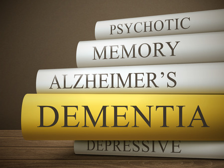 ageing: book title of dementia isolated on a wooden table over dark background