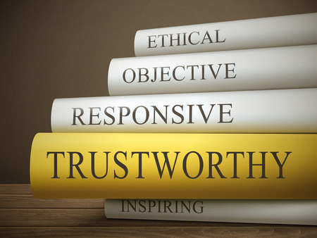 characteristics: book title of trustworthy isolated on a wooden table over dark background