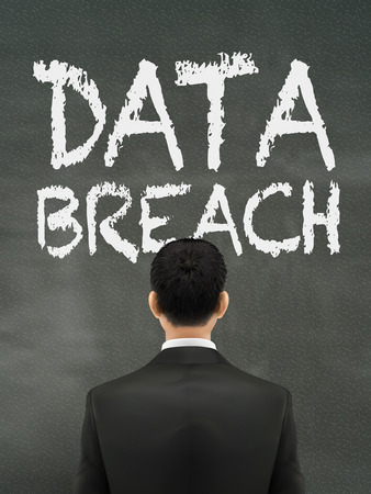 vulnerability: businessman looking at data breach words on wall