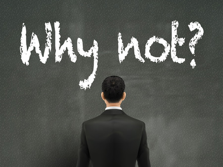 why not: businessman looking at why not words on wall