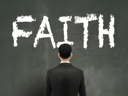 jesus standing: businessman looking at faith word on wall