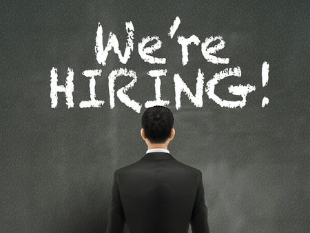 help wanted sign: businessman looking at we are hiring words on wall