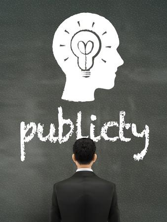 publicity: hombre de negocios mirando palabra publicidad en el muro