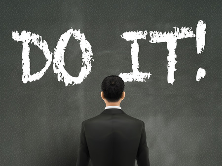 businessman looking at do it words on wall Illustration