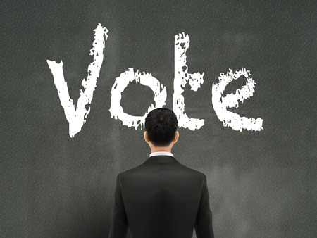 voting rights: businessman looking at vote word on wall