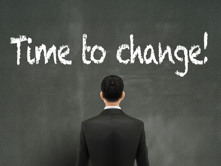 back problem: businessman looking at time to change words on wall Illustration