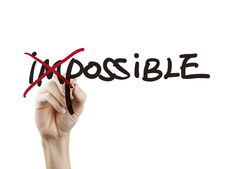 achievable: hand turning the word impossible into possible over white background Stock Photo