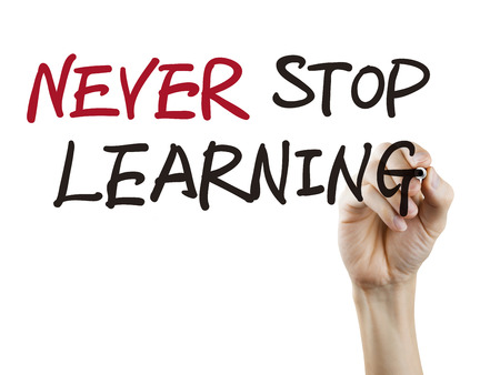 never stop learning words written by hand over white background photo