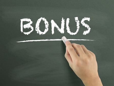additional compensation: bonus word written by hand on blackboard