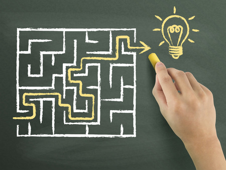 complex navigation: yellow arrow going through a maze drawn by hand isolated on blackboard