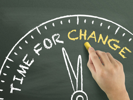 time to change written by hand on blackboard Stock Photo