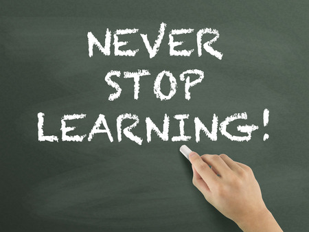never: never stop learning written by hand on blackboard Stock Photo