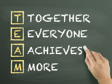achieves: Together Everyone Achieves More written by hand on blackboard Stock Photo