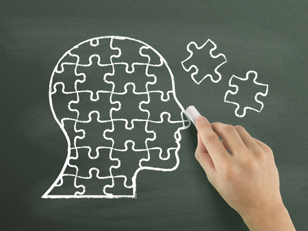 health answers: puzzles in head shape drawn by hand over chalkboard