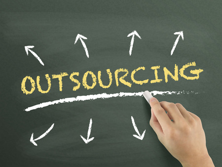 outsourcing: outsourcing word written by hand over chalkboard