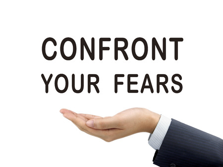 confront: confront your fears words holding by businessmans hand over white background