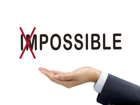 achievable: turning the word impossible into possible by businessmans hand over white background