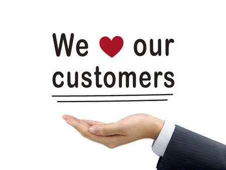 our: we love our customers words holding by businessmans hand over white background Stock Photo