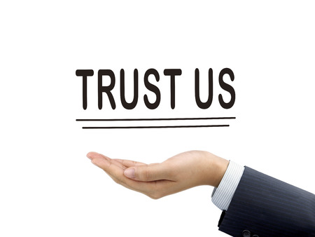 trustworthiness: trust us words holding by businessmans hand over white background Stock Photo