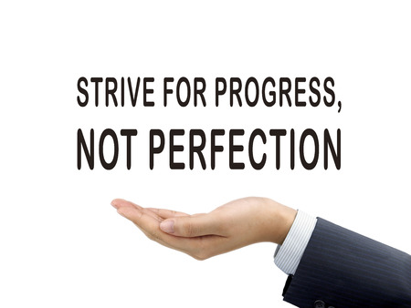 strive for progress not perfection words holding by businessmans hand over white background Stock Photo