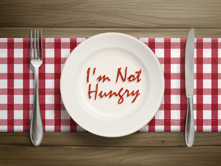 starvation: top view of I am not hungry written by ketchup on a plate over wooden table