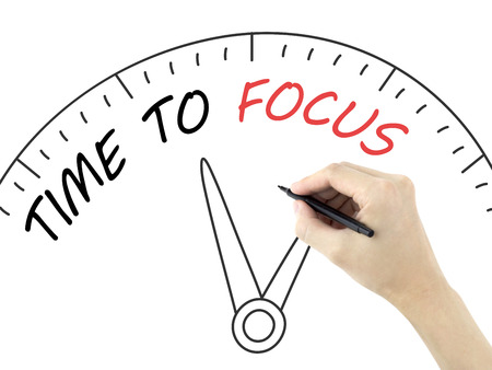 distinctness: time to focus written by mans hand on white background