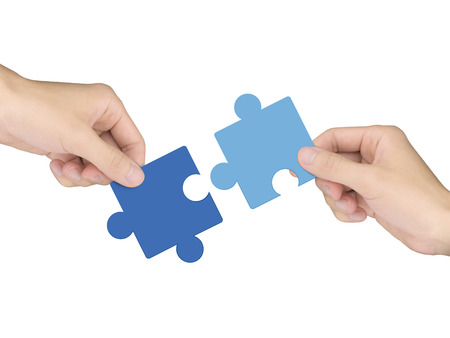 cooperation concept: hands holding jigsaw pieces over white background