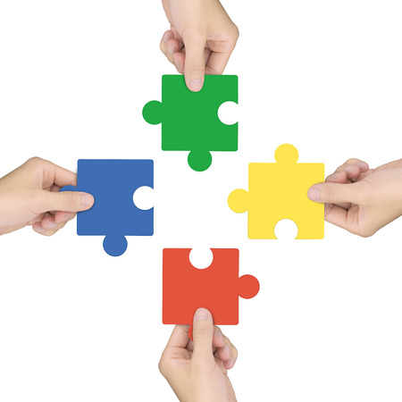 combining: cooperation concept: hands holding jigsaw pieces over white background