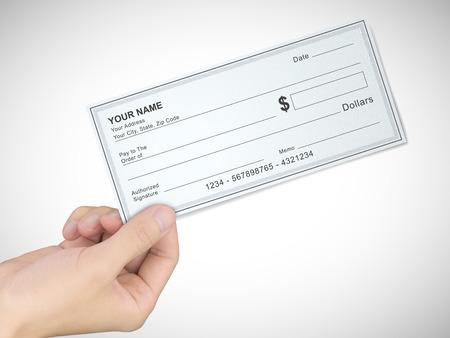 cheque en blanco: concepto de negocio: La mano del hombre que sostiene un cheque sobre fondo gris
