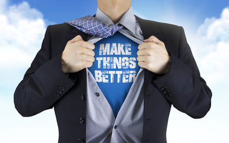 underneath: businessman showing Make things better words underneath his shirt over blue sky