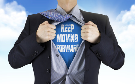 resilience: businessman showing Keep moving forward words underneath his shirt over blue sky