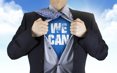perseverance: businessman showing We can words underneath his shirt over blue sky Stock Photo