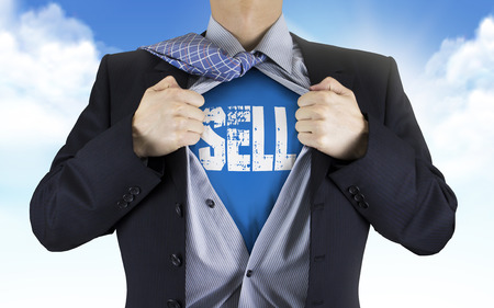 underneath: businessman showing Sell word underneath his shirt over blue sky