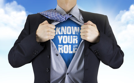 businessman showing Know your role words underneath his shirt over blue sky