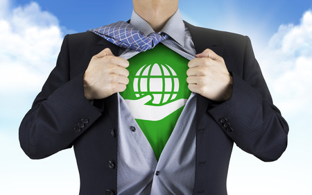 underneath: businessman showing earth icon underneath his shirt over blue sky
