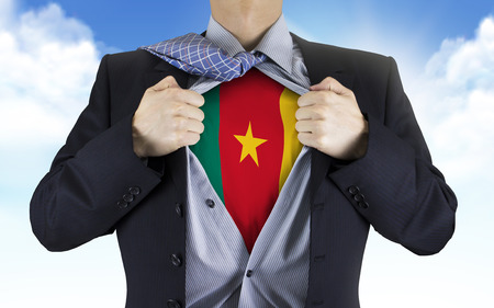 underneath: businessman showing Cameroon flag underneath his shirt over blue sky Stock Photo