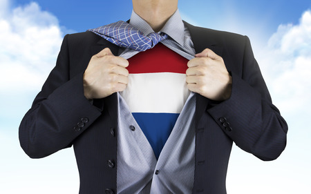 underneath: businessman showing Dutch flag underneath his shirt over blue sky Stock Photo
