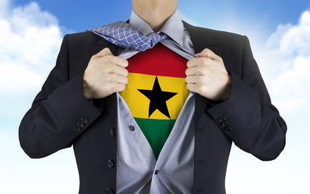 businessman showing Ghana flag underneath his shirt over blue sky photo
