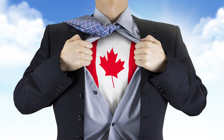 canada flag: businessman showing Canada flag underneath his shirt over blue sky Stock Photo