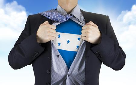 bandera honduras: de negocios que muestra la bandera de Honduras debajo de su camisa sobre el cielo azul Foto de archivo