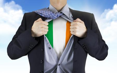 businessman showing Ireland flag underneath his shirt over blue sky photo