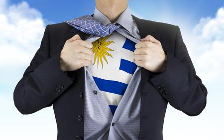 underneath: businessman showing Uruguay flag underneath his shirt over blue sky